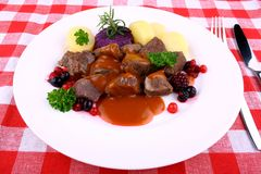 Red deer goulash with potato, Burgundy sauce and wild berries Stock Photo