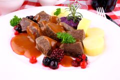 Red deer goulash with potato, Burgundy sauce and wild berries Royalty Free Stock Photos