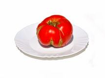 Red defect tomato. On white plate Royalty Free Stock Photography