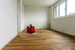 Red dehumidifier in an empty room with a toxic mold and mildew problem. Red dehumidifier in an empty apartment room with a toxic mold and mildew problem Royalty Free Stock Images