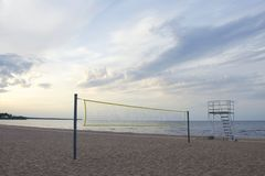 Red del voleibol de los deportes y torre del rescate en una playa arenosa fotografía de archivo