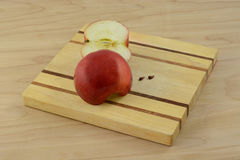 Red Delicious apple halves and apple seeds. On wooden cutting board royalty free stock photos