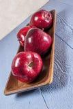 Red delicious, manzanas, tabla de madera azul Imagenes de archivo