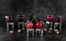 Red delicious ripe cherries on silver chairs with cherrystones o Stock Photo