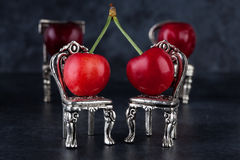 Red delicious ripe cherries on silver chairs and dark background Stock Photos