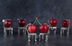 Red delicious ripe cherries on silver chairs and dark background Stock Image