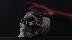 Red demon hand touching the skull. Black background. 4K stock video footage