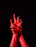 Red demonic hands with black nails, real body-art. Red demonic hands with black nails, Halloween theme, isolated on black background Stock Photo