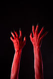 Red demonic hands with black nails, real body-art. Red demonic hands with black nails, Halloween theme, studio shot on black background Royalty Free Stock Photography