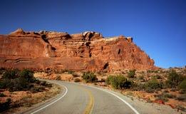 Red desert road. Road through Arches National Park, Utah Stock Photos
