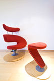 Red designer armchair. Detail of a red designer armchair with wooden base stock photos