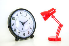Red desk lamp focusing on alarm clock Royalty Free Stock Image