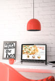 Red desktop with laptop showing pizza order online website Royalty Free Stock Photo