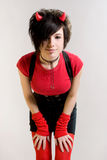 Red devil. A young sexual girl in an image of a devil  in red and black with  horns on her head posing on a light background Stock Image
