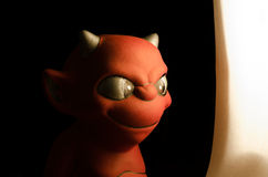 Red devil figurine looking into the light.  on black. Royalty Free Stock Image