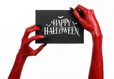 Red devil hand with black nails holding a paper card with the words Happy Halloween Stock Photos
