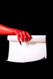 Red devil hand with black nails holding paper scroll. Deal with devil concept royalty free stock photo