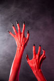 Red devil hands with black nails, extreme body-art. Red devil hands with black nails, Halloween theme, studio shot over smoky background Royalty Free Stock Photos