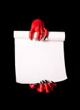 Red devil hands with black nails holding blank paper scroll. Red devil hands holding paper scroll, deal with devil concept, isolated on black background stock photo
