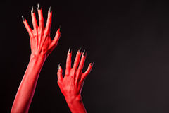 Red devil hands with black nails, real body-art. Red devil hands with black nails, Halloween theme, studio shot on black background Stock Image