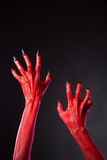 Red devil hands with black nails, real body-art. Red devil hands with black nails, Halloween theme, studio shot on black background Royalty Free Stock Image