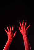 Red devil hands with black nails, real body-art. Red devil hands with black nails, Halloween theme, studio shot on black background Royalty Free Stock Photo