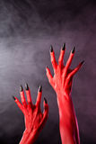 Red devil hands with black nails, real body-art. Red devil hands with sharp black nails, Halloween theme, studio shot over smoky background Royalty Free Stock Images