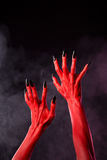 Red devil hands with black sharp nails, extreme body-art. Red devil hands with black sharp nails, Halloween theme, studio shot over smoky background Royalty Free Stock Images