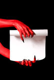 Red devil hands holding paper scroll. Deal with devil concept royalty free stock image