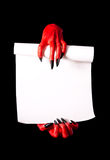 Red devil hands holding paper scroll Royalty Free Stock Photo