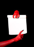 Red devil hands holding paper scroll Stock Photo