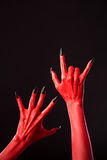 Red devil hands with long black nails, real body-art. Red devil hands with long black nails, Halloween theme, studio shot on black background Royalty Free Stock Images