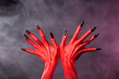 Red devil hands with sharp black nails, extreme body-art. Studio shot over smoky background Stock Photos