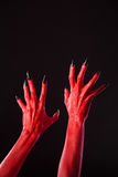 Red devil hands with sharp black nails, real body-art. Red devil hands with sharp black nails, Halloween theme, studio shot on black background Royalty Free Stock Photos