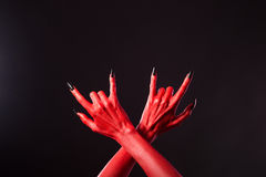 Red devil hands showing heavy metal gesture Stock Images