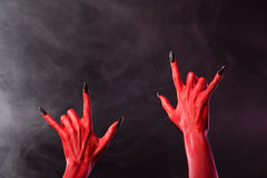 Red devil hands showing heavy metal gesture. Studio shot on smoky background Stock Images