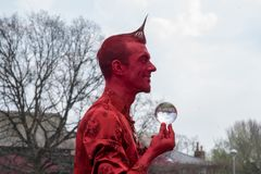 Red devil perfomance artist with crystal ball balanced on fingertips. Stratford upon Avon Warwickshire England UK April 21st 2018 Shakespeares Birthday royalty free stock image