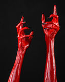 Red Devil's hands with black nails, red hands of Satan, Halloween theme, on a black background, isolated Stock Images