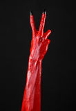 Red Devil's hands with black nails, red hands of Satan, Halloween theme, on a black background, isolated Stock Image