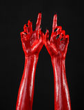 Red Devil's hands with black nails, red hands of Satan, Halloween theme, on a black background, isolated Royalty Free Stock Photography