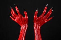 Red Devil's hands with black nails, red hands of Satan, Halloween theme, on a black background, isolated Royalty Free Stock Images