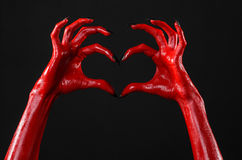 Red Devil's hands with black nails, red hands of Satan, Halloween theme, on a black background, isolated. Studio Royalty Free Stock Photo