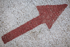 Red diagonal arrow on a textured wall Royalty Free Stock Images