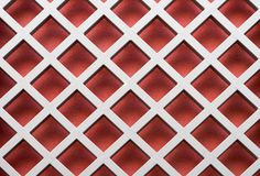 Red diagonal pattern. Image of a metal lattice over a red wall royalty free stock image