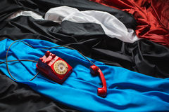Red dial phone on a crumpled tissue, colored fabrics, raw material, red, black, blue, white cloth, Stock Photos