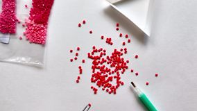 A red diamond mosaic is scattered on a white background. Girl takes mosaic tweezers stock video