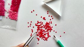 A red diamond mosaic is scattered on a white background. Girl takes mosaic tweezers stock footage