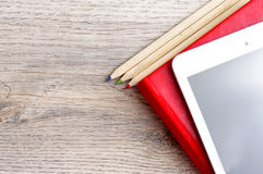 Red diary notebook, white tablet and colored pencils on desk woo Royalty Free Stock Photo