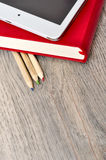 Red diary notebook, white tablet and colored pencils on desk woo Royalty Free Stock Photos