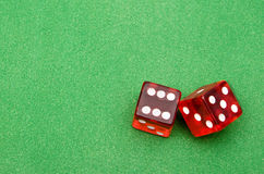 Red dice against green background Royalty Free Stock Images